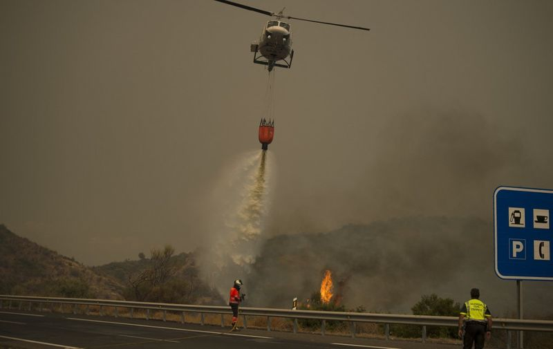 A helicopter drops water over a wildfire in Estepona, Malaga province, on September 9, 2021. - Almost a thousand people had to be evacuated preventively from their homes due to a forest fire in southern Spain, which firefighters continue to fight today, authorities reported. (Photo by JORGE GUERRERO / AFP)