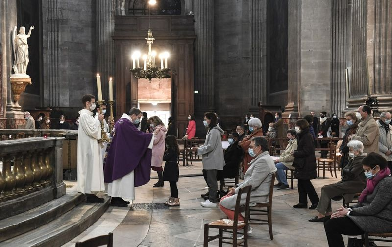 People attend a service at the Saint-Sulpice church in Paris on November 29, 2020 as mass resume in France following the government's ease of Covid-19 lockdown restrictions with only 30 people allowed per church. (Photo by ALAIN JOCARD / AFP)