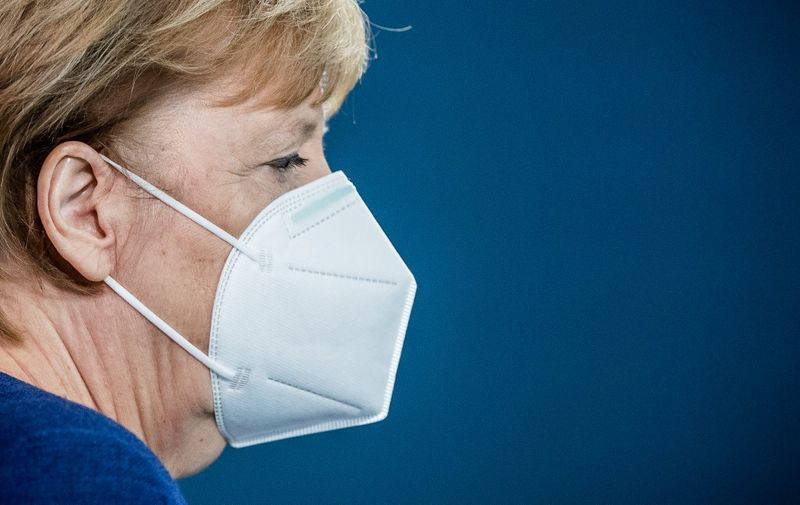 German Chancellor Angela Merkel arrives wearing a face mask to deliver a statement on the outcome of the presidential election in the United States of America, on November 9, 2020 in Berlin. (Photo by Michael Kappeler / POOL / AFP)