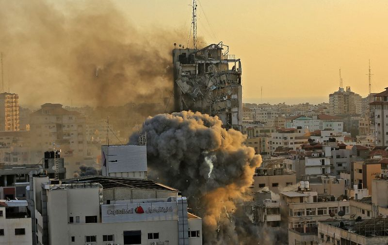 Heavy smoke and fire rise from Al-Sharouk tower as it collapses after being hit by an Israeli air strike, in Gaza City on May 12, 2021. - An Israeli air strike destroyed a multi-storey building in Gaza City today, AFP reporters said, as the Jewish state continued its heavy bombardment of the Palestinian enclave. (Photo by QUSAY DAWUD / AFP)