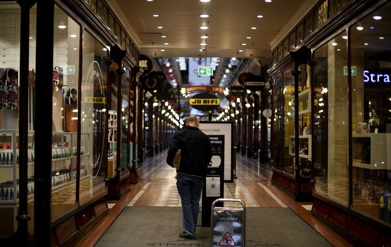 A man sanitizes his hands before entering a quiet shopping mall in the central business district of Sydney on June 28, 2021, during a two-week coronavirus lockdown to contain an outbreak of the highly contagious Delta variant. (Photo by Saeed KHAN / AFP)