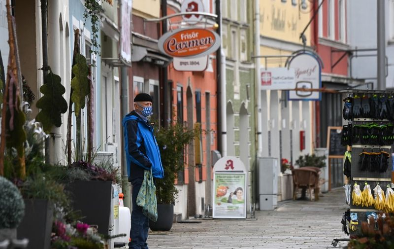A man wears a face mask while standing on a street in Pfarrkirchen, a town of the county district Rottal-Inn in Bavaria, on October 27, 2020 after a local lockdown was imposed because of the coronavirus Covid-19 pandemic. (Photo by Christof STACHE / AFP)