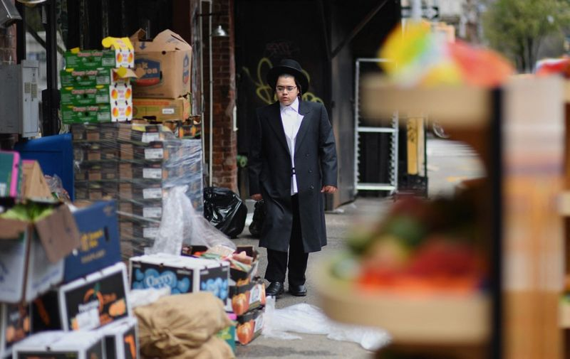 A member of the Orthodox Jewish community passes by a grocery store on April 8, 2020 in Brooklyn, New York, as the Passover holiday starts Wednesday evening and runs to April 16, 2020. - Churches will be empty this Easter and Passover festivities will also take place behind closed doors owing to the COVID-19 lockdown. Christians will be obliged to turn to services broadcast on television or over social media this year owing to the coronavirus and Jews will mark the Passover holiday in their own homes rather than as communities. (Photo by Angela Weiss / AFP)