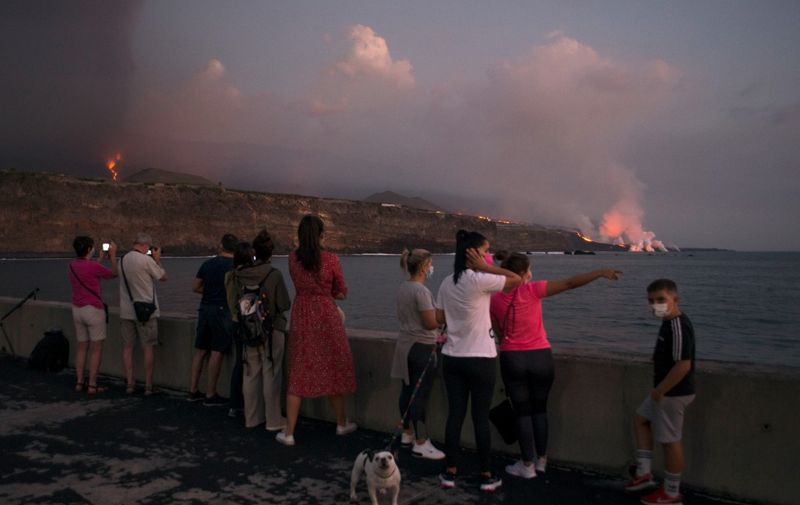 People observe the lava of the Cumbre Vieja volcano falling into the ocean from the port of Tazacorte, in the Canary Island of La Palma on October 6, 2021. - It has been more than two weeks since La Cumbre Vieja began erupting, forcing more than 6,000 people out of their homes as the lava burnt its way across huge swathes of land on the western side of La Palma in Spain's Canary Islands. (Photo by JORGE GUERRERO / AFP)