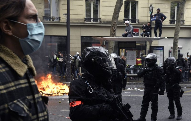 A police officer of the brigade of repression of violent action BRAV holds a brigade of repression of violent action BRAV 40 millimetre rubber defensive bullet launcher (LBD 40) near a fire burning in the street  during the annual May Day (Labour Day) rally in Paris on May 1, 2021. (Photo by Bertrand GUAY / AFP)