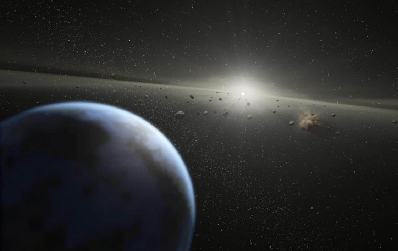 This artist's rendition released 20 April, 2005 by NASA shows a massive asteroid belt in orbit around a star the same age and size as our Sun. Evidence for this possible belt was discovered by NASA's Spitzer Space Telescope when it spotted warm dust around the star, presumably from asteroids smashing together. The view starts from outside the belt, where planets like the one shown here might possibly reside, then moves into to the dusty belt itself. A collision between two asteroids is depicted near the end of the movie. Collisions like this replenish the dust in the asteroid belt, making it detectable to Spitzer. The alien belt circles a faint, nearby star called HD 69830 located 41 light-years away in the constellation Puppis. Compared to our own solar system's asteroid belt, this one is larger and closer to its star - it is 25 times as massive, and lies just inside an orbit equivalent to that of Venus. Our asteroid belt circles between the orbits of Mars and Jupiter.   AFP PHOTO/HO/NASA