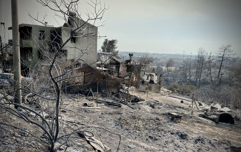 This photograph taken on July 31, 2021 near the town of Manavgat shows burnt houses as a massive forest fire which engulfed a Mediterranean resort region on Turkey's southern coast. - At least three people were reported dead on July 29, 2021 and more than 100 injured as firefighters battled blazes engulfing a Mediterranean resort region on Turkey's southern coast. Officials also launched an investigation into suspicions that the fires that broke out July 28 in four locations to the east of the tourist hotspot Antalya were the result of arson. (Photo by - / AFP)