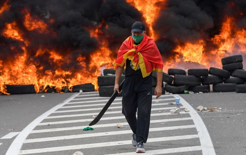 A man walks past burning tires at a barricade set up to block access roads to the historic city of Cetinje during a protest against the inauguration of the new head of the Serbian Orthodox Church on September 5, 2021 in Montenegro. - The new head of the Serbian Orthodox Church in Montenegro was inaugurated, arriving by helicopter under the protection of police who dispersed protesters with tear gas. The decision to anoint Bishop Joanikije as the new Metropolitan of Montenegro at the historic monastery of Cetinje has aggravated ethnic tension in the tiny Balkan state. (Photo by SAVO PRELEVIC / AFP)