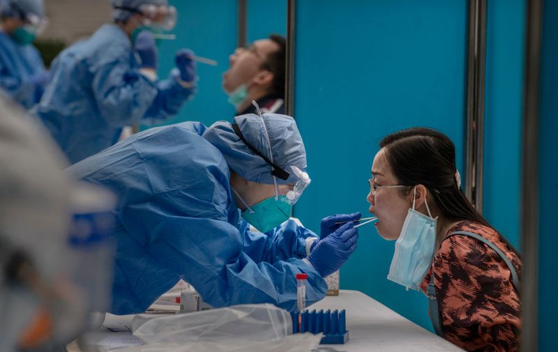 BEIJING, CHINA - MAY 28: Chinese health workers carry out nucleic acid tests on journalists covering events around  the National People's Congress on May 28, 2020 in Beijing, China. China opened its annual parliamentary gathering, known as 'The Two Sessions', at the Great Hall of the People on May 21 after being postponed at the heigh of the coronavirus outbreak in China earlier this year. (Photo by Kevin Frayer/Getty Images)