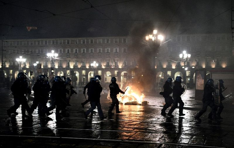Italian police officers stand in front of a wheelie-bin on fire during a protest of far-right activists against the government restriction measures to curb the spread of COVID-19, in downtown Turin, on October 26, 2020, as the country faces a second wave of infections to the Covid-19 (the novel coronavirus). - Italy's Prime Minister Giuseppe Conte tightened nationwide coronavirus restrictions on October 25, 2020 after the country registered a record number of new cases, despite opposition from regional heads and street protests over curfews. Cinemas, theatres, gyms and swimming pools must all close under the new rules, which come into force on October 26, 2020 and run until November 24, while restaurants and bars will stop serving at 6pm, the prime minister's office said. (Photo by Marco BERTORELLO / AFP)