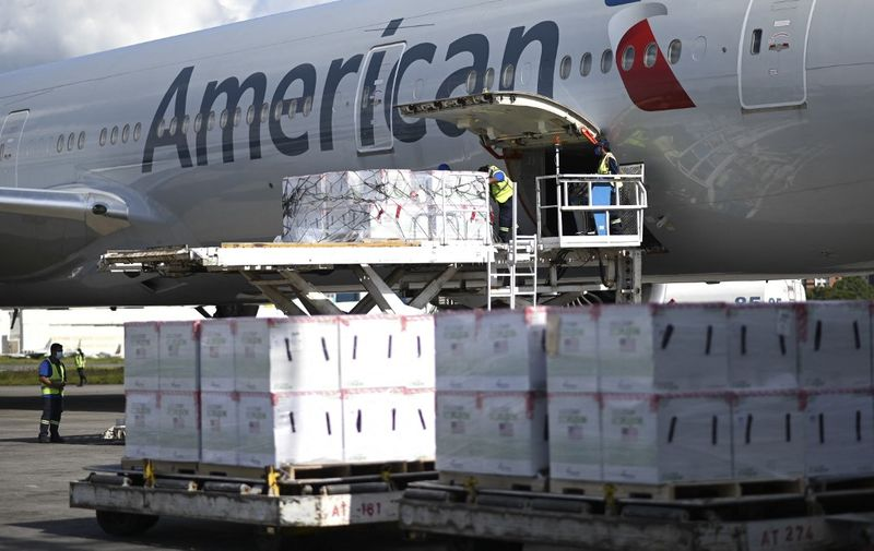 Airport employees unload a batch of three million doses of the Moderna vaccine against COVID-19 donated by the US from an American airlines airplane upon its landing at the Aurora International Airport in Guatemala City, on July 20, 2021. (Photo by Johan ORDONEZ / AFP)