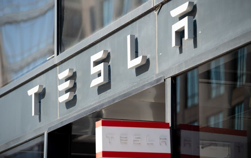 (FILES) In this file photo taken on August 8, 2018 the Tesla logo is seen outside of their showroom in Washington, DC. - Tesla's market value hit $100 billion for the first time on January 22, 2020, triggering a payout plan that could be worth billions for Elon Musk, founder and chief of the electric carmaker. Shares in Tesla rose some 4.8 percent in opening trade to extend the gains in the value of the fast-growing maker of electric vehicles. (Photo by SAUL LOEB / AFP)