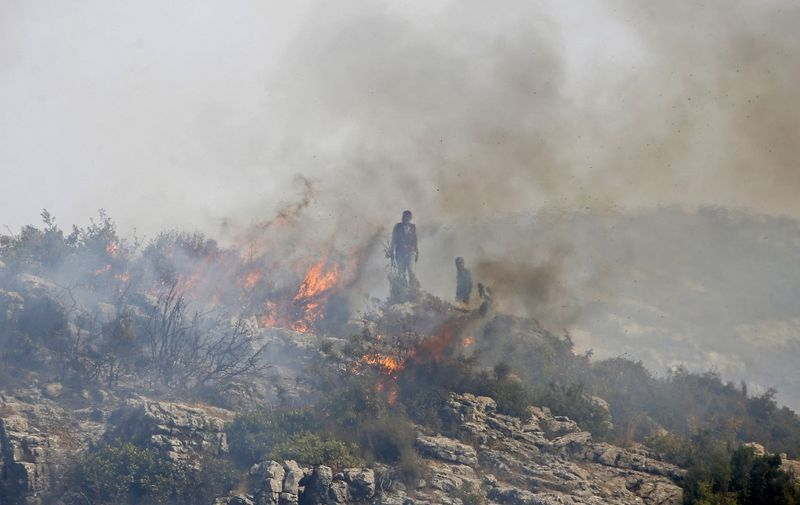 Syrian soldiers and locals battle a forest fire in the Ain Shams area, in the west of Hama province, on September 10, 2020. - Summer fires are common in Syria, but residents have said this year's are worse than usual. (Photo by LOUAI BESHARA / AFP)