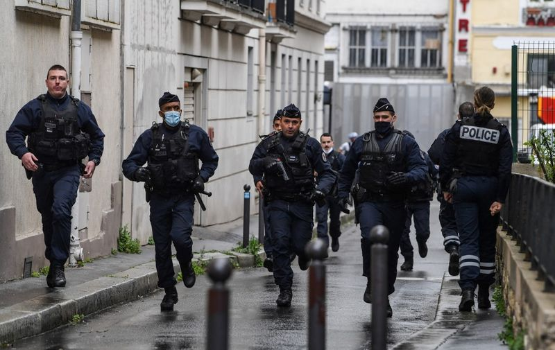 French police officers rush to the scene after people were injured near the former offices of the French satirical magazine Charlie Hebdo following an alleged attack by a man wielding a knife in the capital Paris on September 25, 2020. - A man armed with a knife seriously wounded two people on September 25, 2020, in a suspected terror attack outside the former offices of French satirical weekly Charlie Hebdo in Paris, three weeks into the trial of men accused of being accomplices in the 2015 massacre of the newspaper's staff. Charlie Hebdo had angered many Muslims around the world by publishing cartoons of the Prophet Mohammed, and in a defiant gesture ahead of the trial this month, it reprinted the caricatures on its front cover. (Photo by Alain JOCARD / AFP)