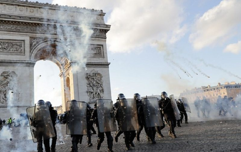 """Riot police charge using tear gas canister at the Arc de Triomphe on the Place de l'Etoile in Paris on March 16, 2019, during clashes with Yellow Vest protesters, on the 18th consecutive Saturday of demonstrations called by the 'Yellow Vest' (gilets jaunes) movement. - Demonstrators hit French city streets again on March 16, for a 18th consecutive week of nationwide protest against the French President's policies and his top-down style of governing, high cost of living, government tax reforms and for more """"social and economic justice."""" (Photo by Thomas SAMSON / AFP)"""
