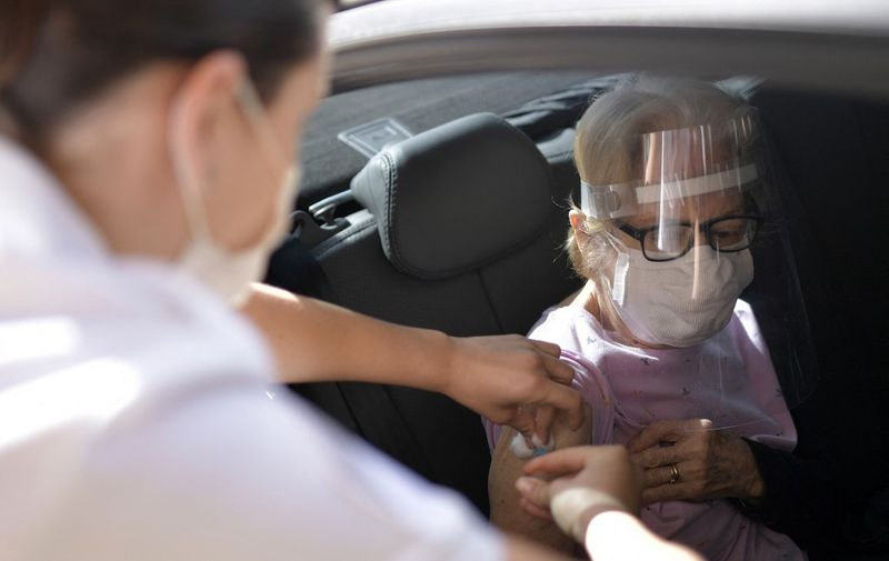 Military personnel of the Brazilian Army vaccinate elderly over 89 years of age, with the second dose of the AstraZeneca/Oxford vaccine against the novel coronavirus, COVID-19, at a drive-through vaccination centre in Belo Horizonte, State of Minas Gerais, Brazil, on May 1, 2021. (Photo by Douglas MAGNO / AFP)