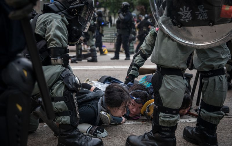 """HONG KONG, CHINA - SEPTEMBER 29: Pro-democracy protesters are arrested by police during clashes after a march on September 29, 2019 in Hong Kong, China. Pro-democracy demonstrations have entered its fourth month as Hong Kong braces for the 70th anniversary of the founding of the People's Republic of China with a series of pro and anti-Beijing protests scheduled towards October 1. Anti-government protesters have continued its call for Chief Executive Carrie Lam to meet their remaining demands, including an independent inquiry into police brutality, the retraction of the word """"riot"""" to describe the rallies, and genuine universal suffrage. (Photo by Chris McGrath/Getty Images)"""