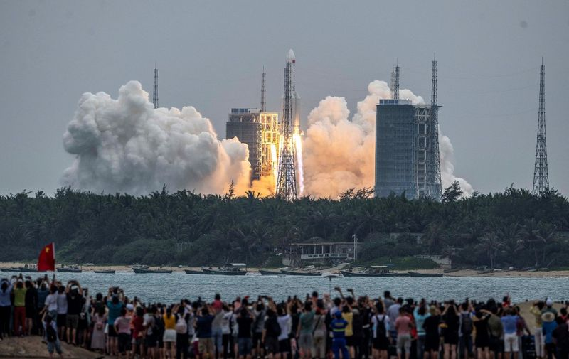 People watch a Long March 5B rocket, carrying China's Tianhe space station core module, as it lifts off from the Wenchang Space Launch Center in southern China's Hainan province on April 29, 2021. (Photo by STR / AFP) / China OUT