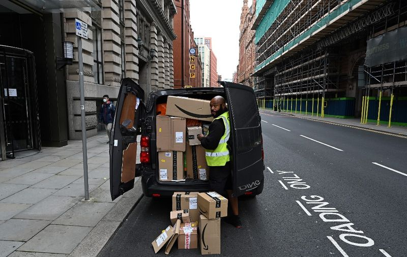 A delivery driver unloads Amazon-branded boxes in Manchester, northwest England as the country battles a surge in coronavirus cases on October 19, 2020 (Photo by Paul ELLIS / AFP)
