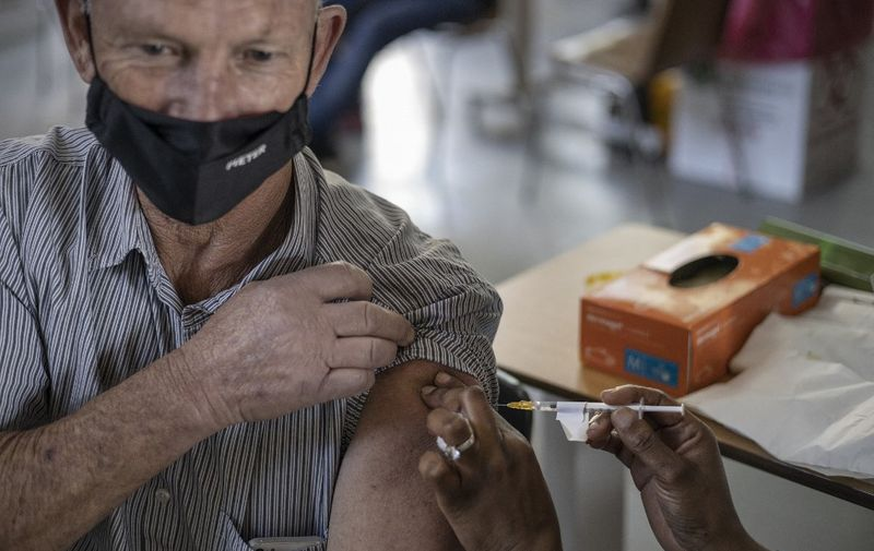A healthcare worker administers a jab containing Pfizer vaccine on an elderly man at the Bertha Gxowa Hospital in Germiston, on May 17, 2021. South Africa is resuming its COVID-19 coronavirus Phase 2 vaccination rollout programme which targets vulnerable groups who are 60 years and older. (Photo by Michele Spatari / AFP)