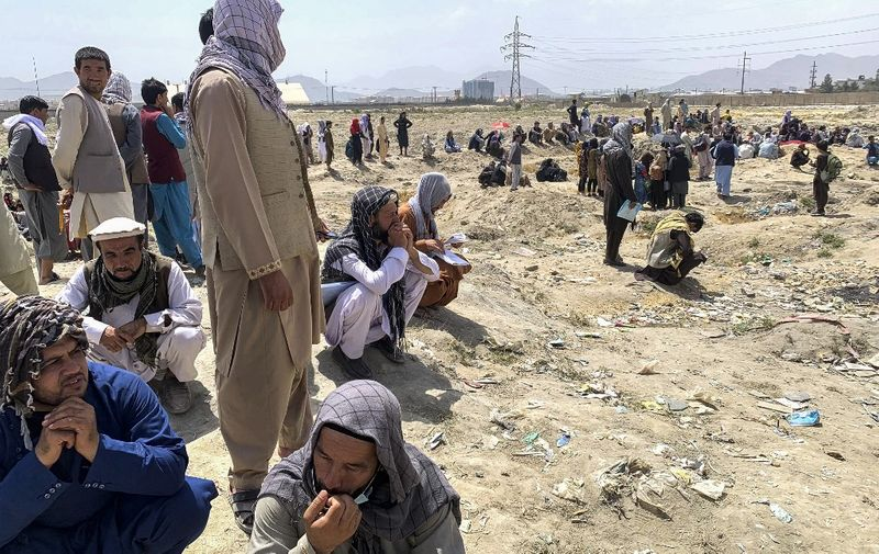 Afghan people gather as they wait to board a U S military aircraft to leave the country, at a military airport in Kabul on August 20, 2021 days after Taliban's military takeover of Afghanistan. (Photo by Wakil KOHSAR / AFP)