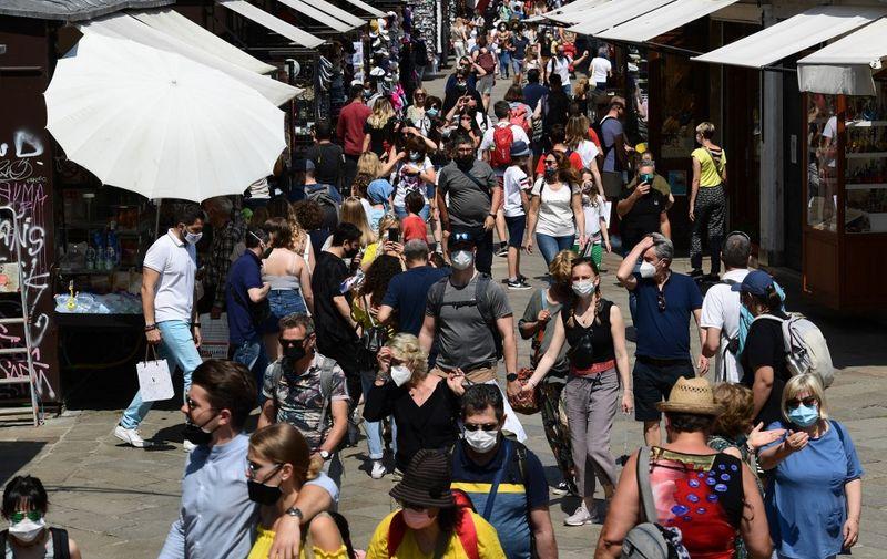 Tourists stroll across the Ruga dei Oresi shopping street near the Rialto bridge in Venice on June 05, 2021. (Photo by MIGUEL MEDINA / AFP)