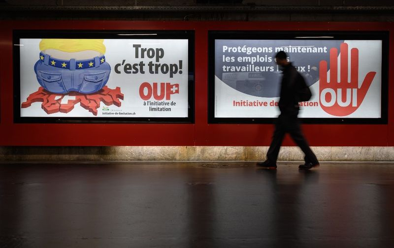 """A picture taken on September 1, 2020 in Lausanne shows backlit electoral posters that translates from French as """"Too much is too much!"""" (L) and """"Protecting the jobs of local workers now"""" to advertise a right-wing Swiss People's Party (SVP)-backed initiative that voted on September 27, 2020 demanding that the government scrap the freedom of movement agreement with the EU within a year. - A large majority of Swiss voters rejected on September 27, 2020 a bid to dramatically reduce immigration from the European Union, amid fears it would have jeopardised relations with the bloc, projections showed. (Photo by Fabrice COFFRINI / AFP)"""