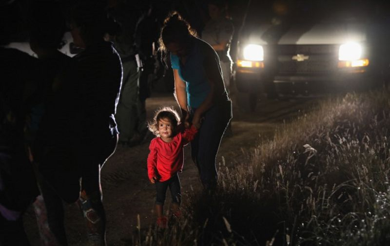 """MCALLEN, TX - JUNE 12: A two-year-old Honduran stands with her mother after being detained by U.S. Border Patrol agents near the U.S.-Mexico border on June 12, 2018 in McAllen, Texas. The asylum seekers had rafted across the Rio Grande from Mexico and were detained before being sent to a Border Patrol processing center for possible separation. Customs and Border Protection (CBP) is executing the Trump administration's """"zero tolerance"""" policy towards undocumented immigrants. U.S. Attorney General Jeff Sessions also said that domestic and gang violence in immigrants' country of origin would no longer qualify them for political asylum status.   John Moore/Getty Images/AFP"""