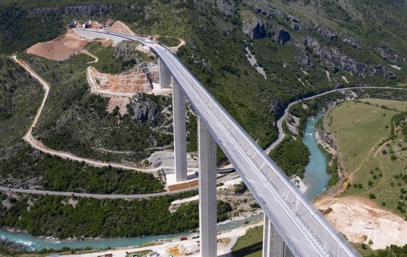 An aerial views shows a part of the new highway connecting the city of Bar on Montenegro's Adriatic coast to landlocked neighbour Serbia, (Bar-Boljare highway) on May 11, 2021, near Matesevo, which is being constructed by China Road and Bridge Corporation (CRBC), the large state-owned Chinese company. - Two sleek new roads vanish into mountain tunnels high above a sleepy Montenegrin village, the unlikely endpoint of a billion-dollar project that is threatening to derail the tiny country's economy. The government has already burnt through $944 million in Chinese loans to complete the first stretch of road, just 41 kilometres (25 miles), making it among the world's most expensive pieces of tarmac. Chinese workers have spent six years carving tunnels through solid rock and raising concrete pillars above gorges and canyons, but the road in effect goes nowhere. Almost 130 kilometres still needs to be built at a likely cost of at least one billion euros ($1.2 billion). (Photo by SAVO PRELEVIC / AFP)