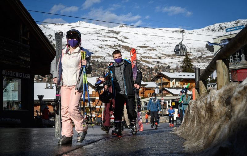 Skiers walk in the Alpine resort of Verbier, well known by British ski holiday makers, on December 22, 2020. - Switzerland on December 21, imposed an entry ban on arrivals from Britain and South Africa and ordered retroactive quarantine for all arrivals from the countries since December 14. The federal government said the move was intended to stop tourism from countries following the discovery there of new, more contagious variants of Covid-19. (Photo by Fabrice COFFRINI / AFP)
