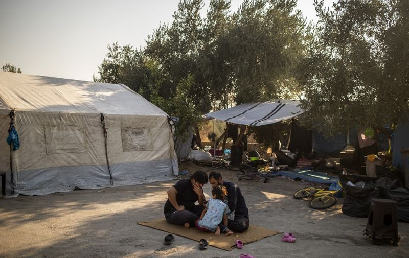 Migrants sit on the ground next to a tent near the burnt Moria refugee camp, on the island of Lesbos on September 13, 2020, a few days after a fire destroyed the camp. - Greece said on September 13 it hoped thousands of asylum seekers left homeless by fires at Europe's largest migrant camp could be rehoused within a week to end a crisis that has seen clashes with police. Asylum-seekers, including the elderly and very young children, have been sleeping rough on Lesbos island since September 9, when some 11,000 fled the overcrowded Moria camp after it was gutted in apparent arson attacks. (Photo by ANGELOS TZORTZINIS / AFP)