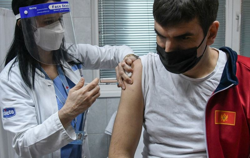 A man receives a dose of Russian-made Sputnik V Covid-19 vaccine in Podgorica on February 22, 2021. (Photo by SAVO PRELEVIC / AFP)