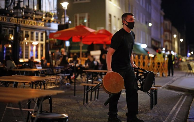 A member of staff takes away stools from outside tables in Soho, in central London on September 24, 2020, on the first day of the new earlier closing times for pubs and bars in England and Wales, introduced to combat the spread of the coronavirus. - Britain has tightened restrictions to stem a surge of coronavirus cases, ordering pubs to close early and advising people to go back to working from home to prevent a second national lockdown. (Photo by Tolga Akmen / AFP)
