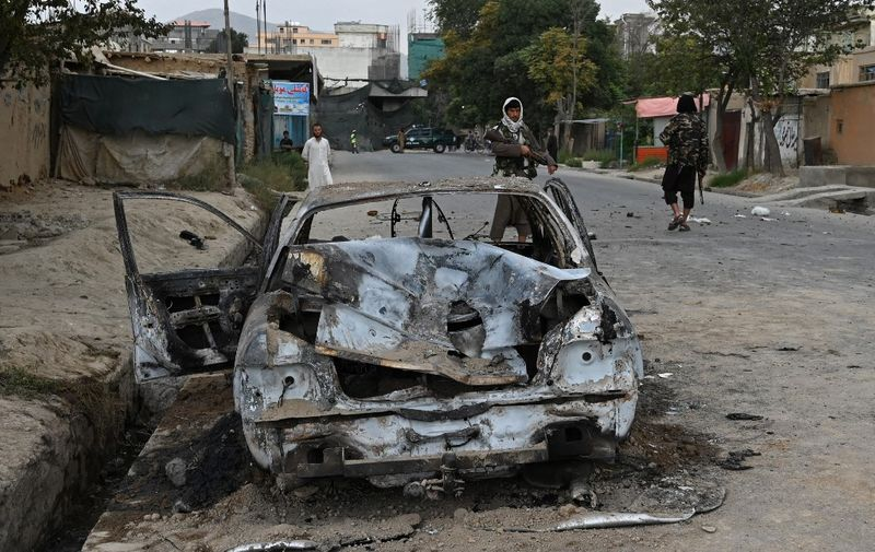 Taliban fighters stand guard near a damaged car after multiple rockets were fired in Kabul on August 30, 2021. - Rockets flew across the Afghan capital on August 30 as the US raced to complete its withdrawal from Afghanistan, with the evacuation of civilians all but over and terror attack fears high. (Photo by WAKIL KOHSAR / AFP)