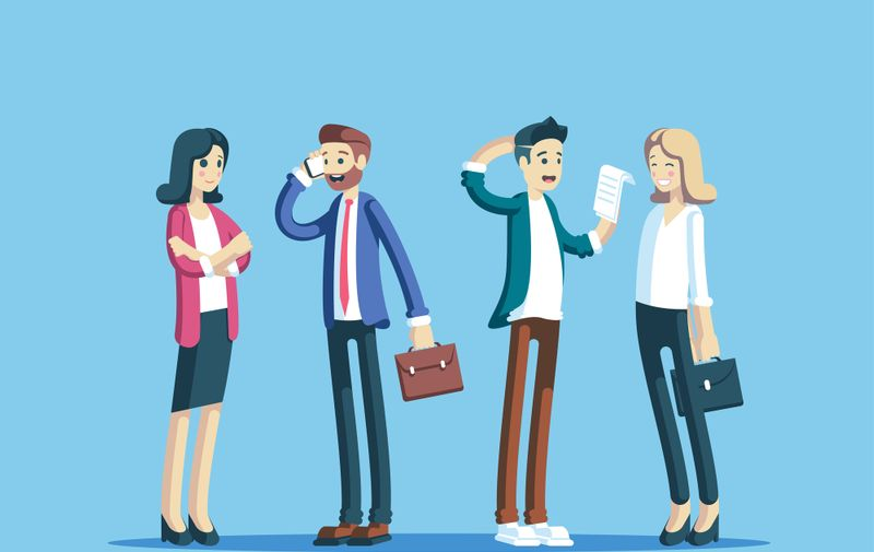 Group of business people standing and smiling. Team of office workers talking to each other. Businesswoman standing with arms crossed, businessman talking on the phone, others study the document.