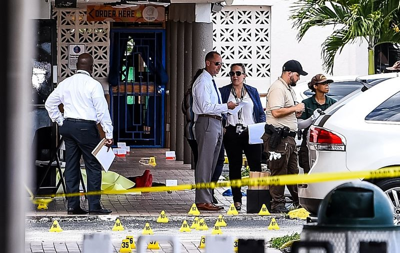 """Miami Dade police officers stand in front of Billiard's club that was rented for a concert, after three gunmen killed two people and injured 20 overnight in the Hialeah area of Miami Dade county on May 30 2021. - Two people were killed and at least 20 injured Sunday when three shooters fired indiscriminately into a crowd outside a concert in Miami, Florida, local police said. Gunfire erupted during the early hours outside a billiards hall in a row of businesses near Miami Gardens, northwest of the coastal city's downtown. People crowded the venue, which was """"hosting a scheduled event and several patrons were standing outside,"""" Miami-Dade Police Department said in a statement. (Photo by CHANDAN KHANNA / AFP)"""