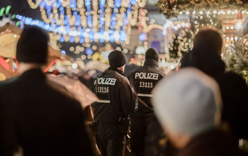 Police patrols at the reopened Christmas market near the Kaiser-Wilhelm-Gedaechtniskirche (Kaiser Wilhelm Memorial Church) in Berlin on December 22, 2016. The Berlin Christmas market that was struck by a deadly truck rampage on December 19, 2016 reopened, as the grieving city sought a return to normal life and police hunted for the prime suspect in the attack. / AFP PHOTO / CLEMENS BILAN
