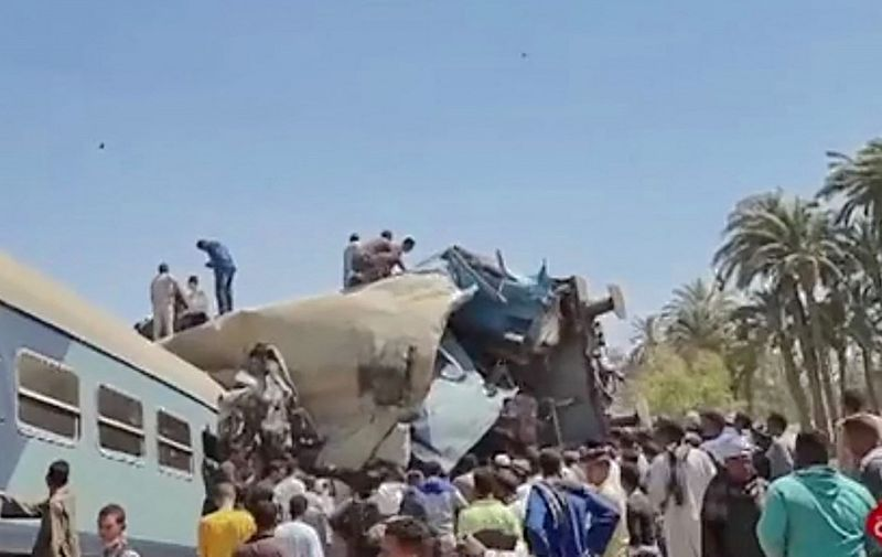 """A video grab taken from the Egyptian state television station shows people gathered around two trains that collided in the Tahta district of Sohag province, some 460 kms (285 miles) south of the Egyptian capital Cairo, reportedly killing at least 32 people and injuring scores of others, on March 26, 2021. - Egypt has been plagued with deadly train accidents in recent years that have been widely blamed on inadequate infrastructure and poor maintenance. (Photo by STRINGER / EGYPTIAN STATE TV / AFP) / XGTY / RESTRICTED TO EDITORIAL USE - MANDATORY CREDIT """"AFP PHOTO / EGYPTIAN TV """" - NO MARKETING - NO ADVERTISING CAMPAIGNS - DISTRIBUTED AS A SERVICE TO CLIENTS"""