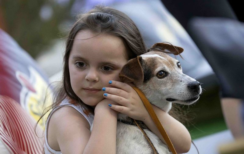 """An Israeli child hugs her dog during a special screening of the movie """"The Secret Life of Pets"""" organised by the Tel Aviv-Jaffa municipality for pets and their owners, on July 11, 2016, at a rooftop cinema theatre in the coastal Israeli city. (Photo by JACK GUEZ / AFP)"""