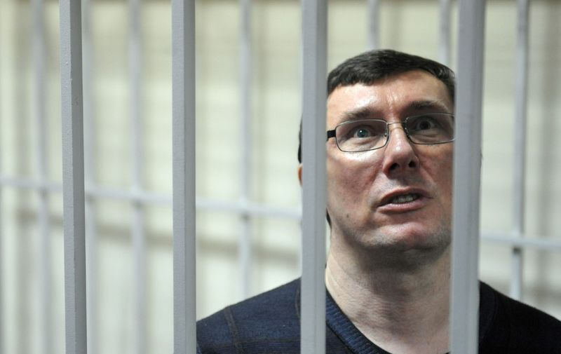 Yuriy Lutsenko, former Ukrainian interior minister ally of the jailed ex-prime minister Yulia Tymoshenko stands in a caged area inside the court during a verdict hearing in Kiev on February 27, 2012.  Lutsenko, who was arrested in December 2010 and has been held in detention ever since, was found guilty by a district court in Kiev of abusing his powers while in office was sentenced to four years in jail in a trial denounced by her supporters as politically motivated.. AFP PHOTO/ SERGEI SUPINSKY (Photo by SERGEI SUPINSKY / AFP)