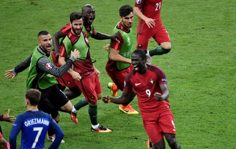 Portugal's forward Eder (R) celebrates after scoring a goal with team mates next to France's forward Antoine Griezmann (L) during the Euro 2016 final football match between Portugal and France at the Stade de France in Saint-Denis, north of Paris, on July 10, 2016. / AFP PHOTO / PHILIPPE LOPEZ