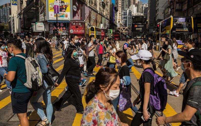 People wearing face masks as a preventative measure against the COVID-19 coronavirus cross a street in the Causeway Bay shopping district in Hong Kong on May 1, 2020. (Photo by DALE DE LA REY / AFP)