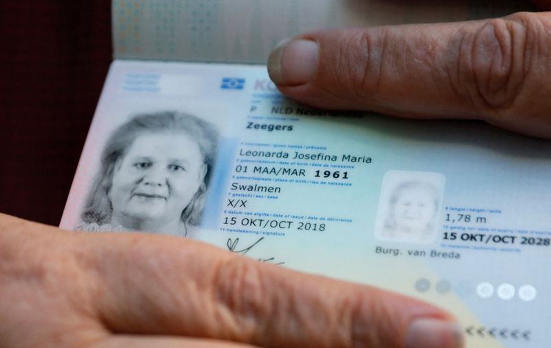 Leonne Zeegers, 57, receives a passeport with the gender designation X, instead of M for man or V for woman in Breda, on October 19, 2018. - The first gender-neutral passport of The Netherlands was issued. (Photo by Bas Czerwinski / ANP / AFP) / Netherlands OUT