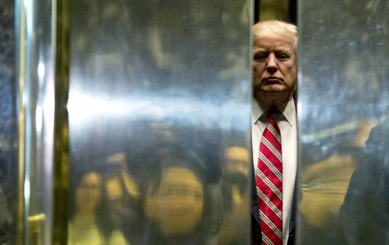 (FILES) In this file photo taken on January 16, 2017, US President-elect Donald Trump boards the elevator after escorting Martin Luther King III to the lobby after meetings at Trump Tower in New York City. - Incumbent US President Donald Trump has been denied a second term after challenger, former US Vice President Joe Biden won the election, TV networks projected on November 7, 2020, a victory sealed after the Democrat claimed several key battleground states won by the Republican incumbent in 2016. CNN, NBC News and CBS News called the race in his favor, after projecting he had won the decisive state of Pennsylvania. His running mate, US Senator Kamala Harris, has become the first woman US Vice President elected to the office. (Photo by DOMINICK REUTER / AFP)