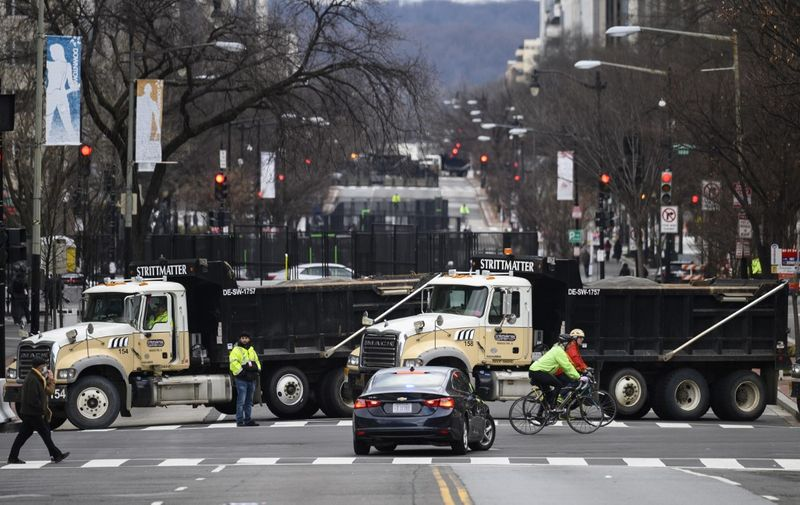 People pass by trucks set up to block a street ahead of the inauguration in Washington, DC on January 17, 2021, during a nationwide protest called by anti-government and far-right groups supporting US President Donald Trump and his claim of electoral fraud in the November 3 presidential election. - The FBI warned authorities in all 50 states to prepare for armed protests at state capitals in the days leading up to the January 20 presidential inauguration of President-elect Joe Biden. (Photo by Andrew CABALLERO-REYNOLDS / AFP)