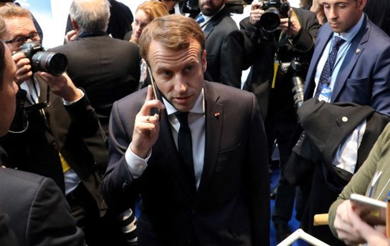 In this photo taken on November 17, 2017 France's President Emmanuel Macron (C) speaks on the phone during the European Social Summit in Gothenburg, Sweden. - French President Emmanuel Macron called an urgent national security meeting on July 22, 2021 to discuss the Israeli-made Pegasus spyware after reports about its use in France emerged this week, a government spokesman said. A consortium of media companies, including the Washington Post, the Guardian and France's Le Monde, reported on Tuesday that one of Macron's phone numbers and those of many cabinet ministers were on a leaked list of potential Pegasus targets. (Photo by ludovic MARIN / AFP)