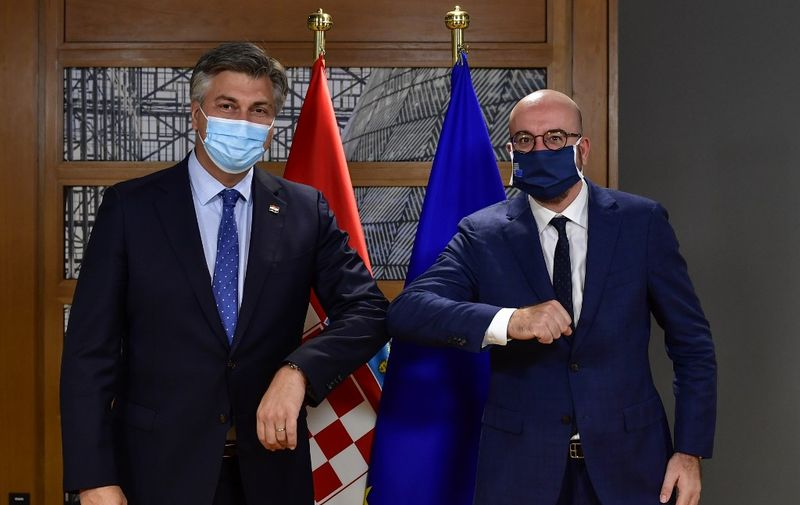 European Council President Charles Michel (R) touches elbows as he greets Croatia's Prime Minister Andrej Plenkovic ahead of a bi-lateral meeting on the first day of a European Union (EU) summit at The European Council Building in Brussels on October 1, 2020. (Photo by JOHN THYS / various sources / AFP)