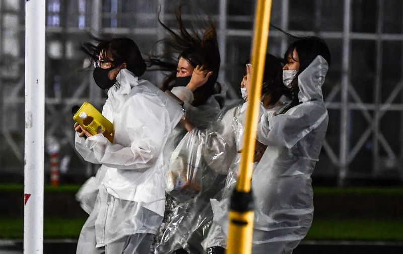 Women walk in heavy rain as Typhoon Haishen hits Kagoshima, Kagoshima prefecture on September 6, 2020. - Typhoon Haishen began to lash southern Japan on September 6, with officials warning it could bring record rainfall and winds strong enough to snap power line poles and flip cars. (Photo by CHARLY TRIBALLEAU / AFP)
