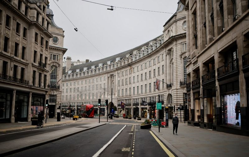 A man wearing a facemask walks along a near-deserted Regent Street, central London on January 8, 2021, as England entered a third lockdown due to the novel coronavirus Covid-19. - Faced by a sharp rise in coronavirus infections, driven by the new strain, England entered a strict lockdown on January 5, 2021, with schools and non-essential shops closed for at least six weeks after previous measures failed to halt the steep rise in cases. (Photo by Tolga Akmen / AFP)