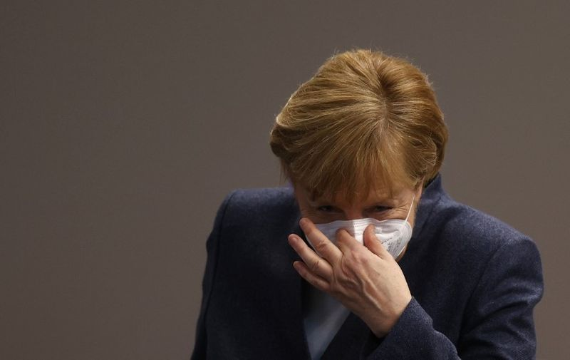 """(FILES) In this file photo taken on December 16, 2020 German Chancellor Angela Merkel puts her face protection mask on after a session of the Bundestag (lower house of parliament) in Berlin, amid the coronavirus Covid-19 pandemic. - Chancellor Angela Merkel on January 16, 2021 said significantly tougher measures were needed to slow Germany's coronavirus infections, party sources told AFP. Speaking at a meeting with top brass from her centre-right CDU party, Merkel said """"the virus can only be stopped with significant additional efforts"""", participants told AFP, adding that the chancellor wanted to hold fresh crisis talks with regional leaders next week. (Photo by Odd ANDERSEN / AFP)"""
